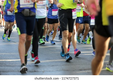 Marathon running race. Legs and bodies only. Unrecognizable people. The marathon is a long-distance running race with an official distance of 42.195 kilometres (26.219 miles, or 26 miles 385 yards).