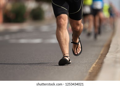 Marathon running race, man running marathon in flip flops, non-sport shoes