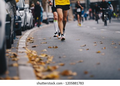 Marathon running race, people feet on autumn road. Runners run urban marathon in the the city. Group of active people running marathon race in the city. Leaves fallen from the trees lying on the road
