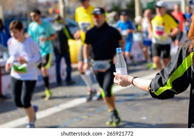 Marathon running race, runners on road, volunteer giving water on refreshment point