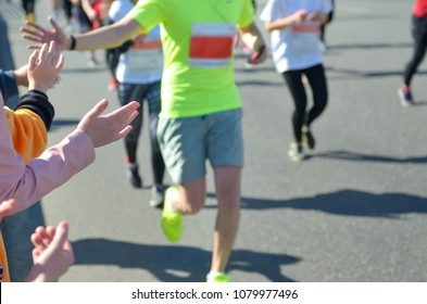 Marathon running race, support runners on road, child's hand giving highfive, sport concept