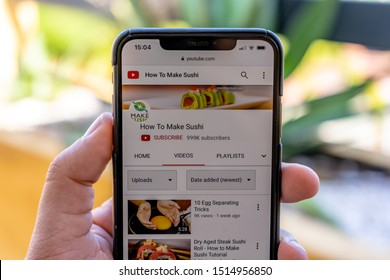 "marbella, malaga/spain - 09 26 2019: iphone xs max open on youtube showing a famous youtube channel ""how to make sushi"" at 999,000 subscribers, mans hand holding smartphone showing youtube channel"