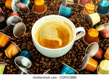 marbella, malaga/spain - 10 23 2019:  espresso coffee in white cup surrounded by various nespresso coffee capsules on a background of coffee beans, nespresso brand coffee