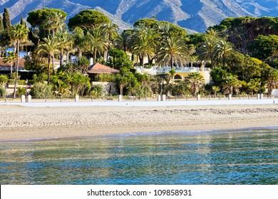 Marbella sandy beach coastline summer holiday scenery by the Mediterranean Sea in Spain, Andalusia region, Costa del Sol, Malaga province.