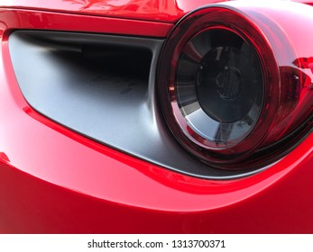 Marbella, Spain - August 10, 2018: Part of a red Ferrari car parked inside the famous Puerto Banus. Luxury port where you can take a walk, have a drink and see large and luxurious yachts