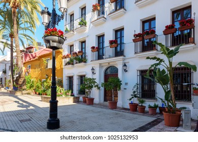 MARBELLA, SPAIN - DECEMBER 2017: Street with beautiful facades, decorated with flower pots