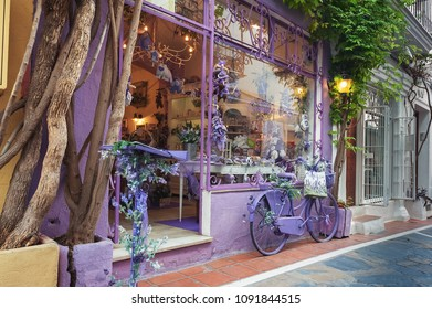 MARBELLA, SPAIN - DECEMBER 2017: Violet souvenir shop facade, decorated with violet bicycle  parked near wall