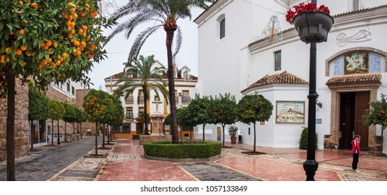 Marbella, Spain - December 25, 2013: Lonely tourist on christmas day in front of the 'Iglesia Mayor de la Encarnacion'. Orange trees line the Plaza de la Iglesia, in the old town centre.