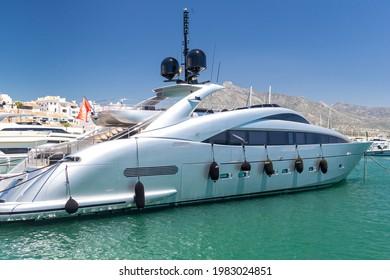"Marbella, SPAIN - July 16 2020: Luxury grey yacht docked in Puerto Jose Banus Harbour, In background ""La Concha"" mountain. Luxury travel destination on Marbella - Malaga , Costa del Sol"