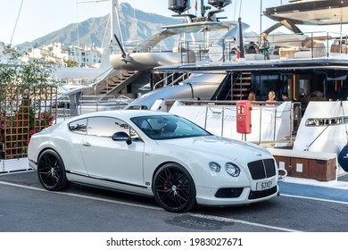 Marbella, SPAIN - July 16 2020: Luxury Puerto Jose Banus Harbour situated in Nueva Andalucia area of Marbella city. Expensive yacht docked, white Bentley parked near. Luxury lifestyle on Costa del Sol