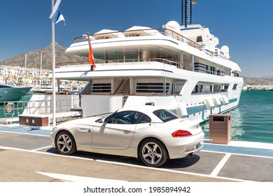 Marbella, SPAIN - July 16 2020: Luxury Puerto Jose Banus Harbour situated in Nueva Andalucia area of Marbella city. Expensive yacht docked, white BMW parked near. Luxury lifestyle on Costa del Sol