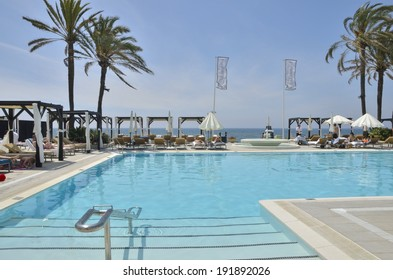 MARBELLA, SPAIN - MAY 1: People quietly sunbathing on May 1, 2014 on a beach club in Marbella, Andalusia, Spain