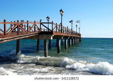 MARBELLA, SPAIN - NOVEMBER 12, 2008 - Wooden pier leading into the sea from Daitona beach, Marbella, Costa del Sol, Malaga Province, Andalucia, Spain, Europe, November 12, 2008.