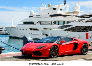 MARBELLA, SPAIN - OCTOBER 13: Front view of a red super sport car (Lamborghini) parked alongside luxury yachts moored in the marina of Puerto Jose Banus, Spain, on October 13, 2016.