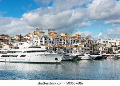 MARBELLA, SPAIN - OCTOBER 13: White expensive luxury yachts moored in the marina of Puerto Jose Banus on the Costa del Sol on a cloudy Autumn morning, on October 13, 2016.