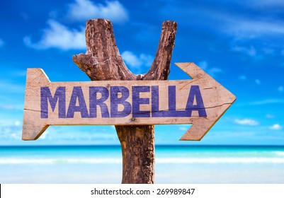 Marbella wooden sign with beach background