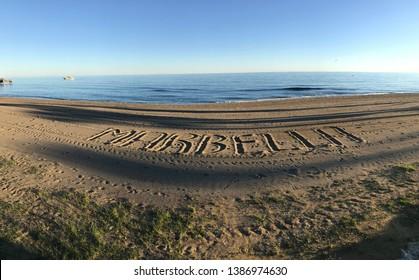 Marbella written in the sand on a beach in marbella