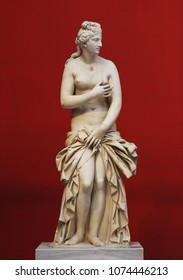 Marble Ancient Greek statue of the Goddess Aphrodite (Venus) on a red background