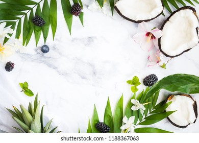 marble background with fresh coconut pieces and palm leaves
