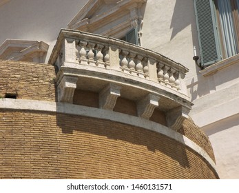 A marble banister is placed on the top of a wall. The wall is made of bricks. The banister is elegant and has a round shape.