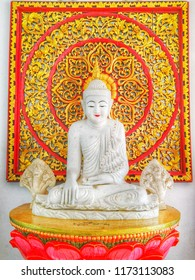 Marble bhudda stute sitting on red lotus behind decorating with Thai art gloden wood stencil.