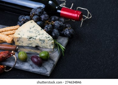 Marble board with cheese selection, wine and grapes on dark background from above