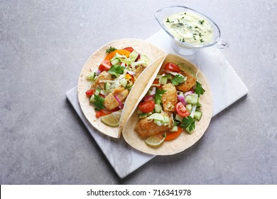 Marble board with tasty fish tacos and sauce on table