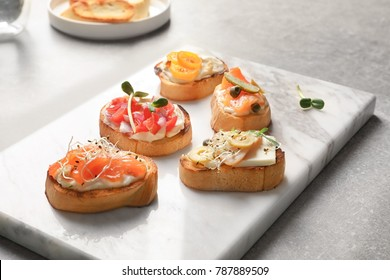 Marble board with tasty fresh bruschettas on table