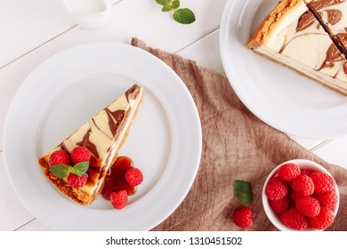 Marble Cheesecake Dessert Raspberry Flat Lay. Chocolate Cocoa Cheese Cake Piece on White Plate Top Down View. Vanilla Pastry Food with Mint Syrup Decorating. Sweet Brown Pie on Wooden Background