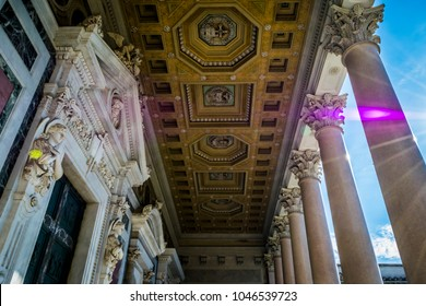 Marble columns, statues and ornate ceiling of St. Paul's Cathedral in Rome, Italy.  Architectural detail, cloudy sky in background.