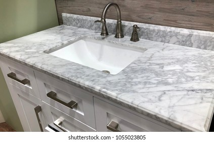 marble countertop with backsplash, white wooden cabinets, chrome faucet and white rectangular under mount sink
