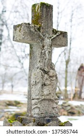 Marble cross on tomb at winter