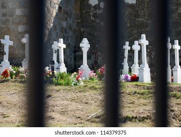 Marble crosses behind bars in rural cemetery