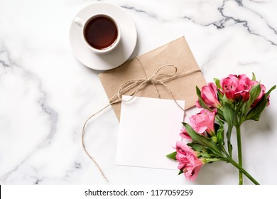 Marble desk with cup of coffee, pink flowers, postcard, kraft envelope, twine, cotton branch, invitation card with copy space for your text. Flat lay, top view. Woman's day or mother's day mockup.