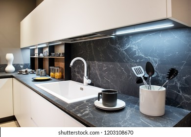Marble effect kitchen counter with utensils and a white rectangular sink below wall mounted cabinets and splash back