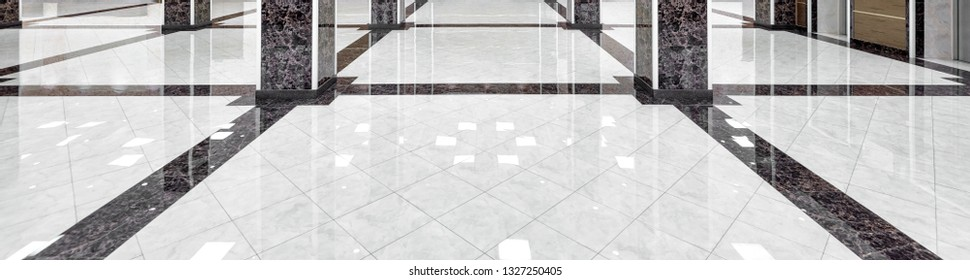 Marble floor of a luxury lobby of company or hotel. Panorama of a cleaned washed floor in corporate hallway. Shiny floor with reflections after professional cleaning. Care service of office interior.