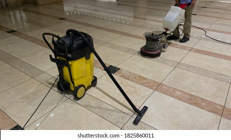 Marble floor polishing with a professional floor scrubber and wet vacuum cleaner in office building lobby