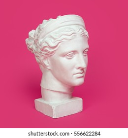 Marble head of young woman, ancient Greek goddess bust isolated on pink background