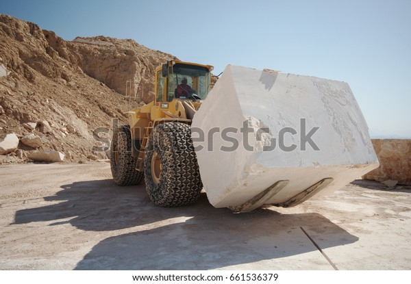Marble industry. Quarry. A bulldozer moving marble block.