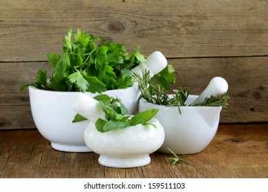 marble mortar with different herbs on a wooden background