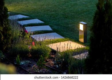 marble path of square tiles illuminated by a lantern made of metal glowing with a warm light in a backyard garden with a flower bed and a lawn.