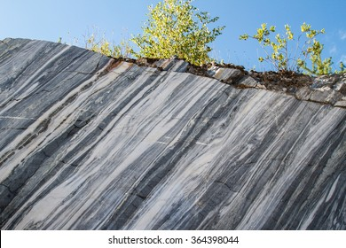 Marble quarry, marble rocks in the wild in the Republic of Karelia. Natural stone. Ancient Marble quarry, marble rocks in the wild. Slices of marble mountain. Trees on the marble rock. Historic place