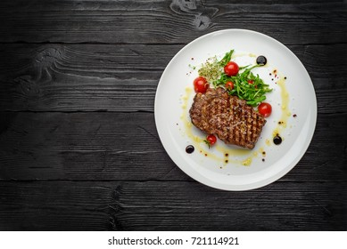Marble stake with spicy herbs and sea salt over dark wooden background