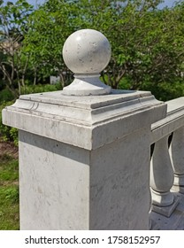 Marble stone ball on fence in park. Balustrades. Rows of white marble balusters. Architecture detail decoration element in classic style. European park garden landscape design.