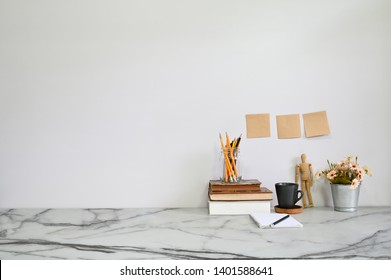 Marble table with books, coffee, flower, pencil and sticky note A Office desk concept.