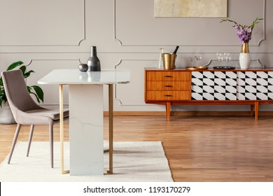 Marble table next to a chair in an eclectic dining room interior with a retro cabinet