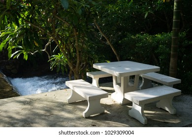 Marble table set with shadow of tree in the garden.