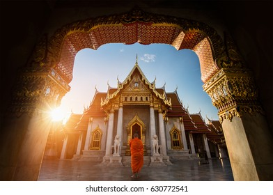 Marble Temple with a Monk in Sunrise Sky in Bangkok of Thailand.