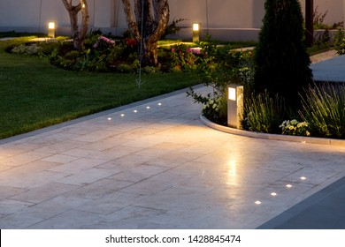 marble tile playground in the backyard of flowerbeds and lawn with ground lantern and lighting in the warm light at dusk in the evening.
