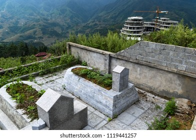 Marble tombstones on Vietnamese cemetery in mountains. Asian graveyard located on the terraces and hills near Sa Pa, Vietnam. Construction site with crane on background.